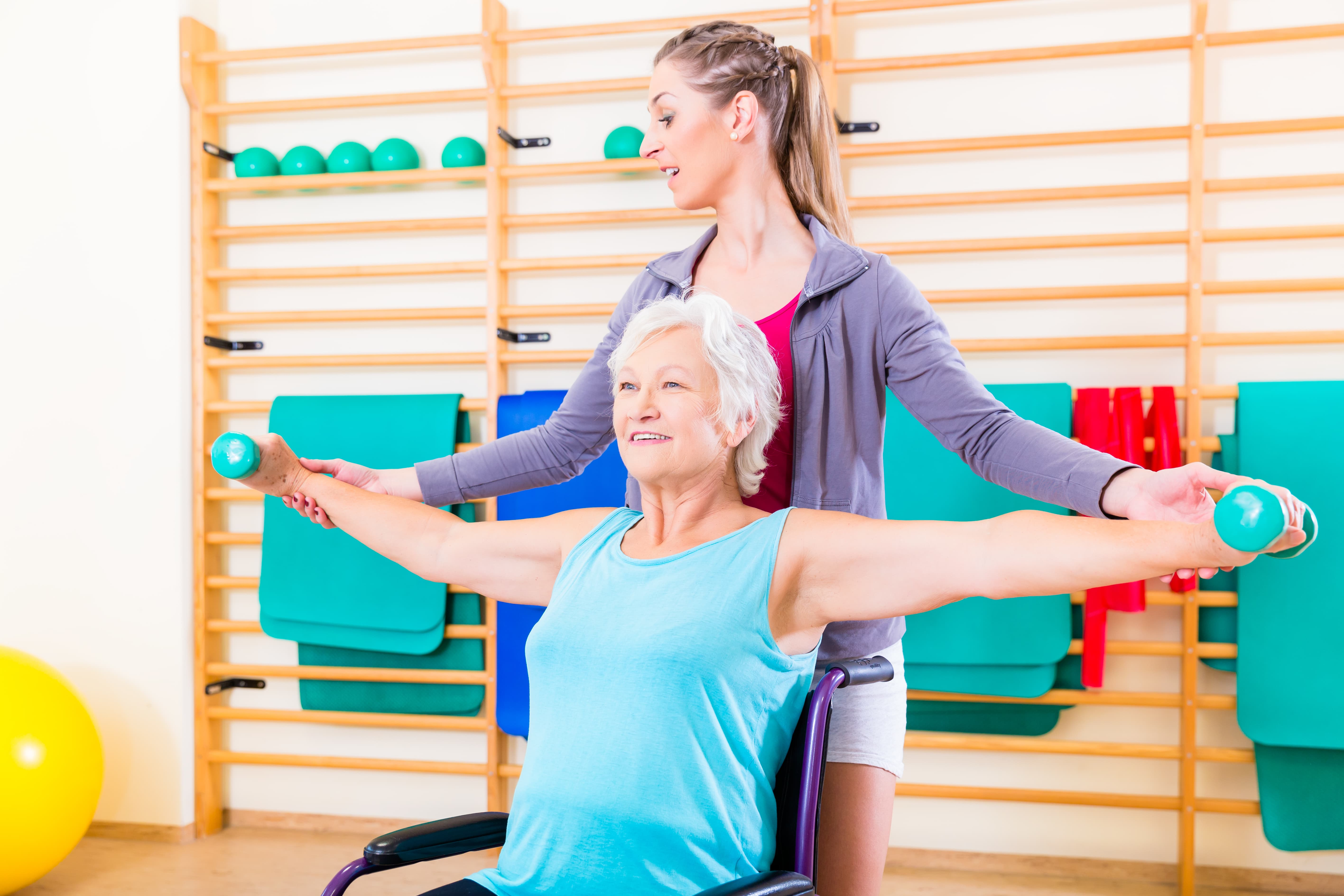 caregiver guiding senior woman exercise